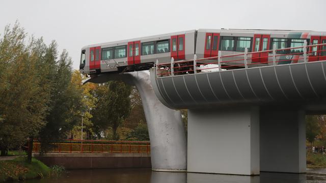 https://media.nu.nl/m/i80x7raas88r_wd640.jpg/metro-schiet-in-spijkenisse-door-stopblok-en-hangt-op-10-meter-hoogte.jpg