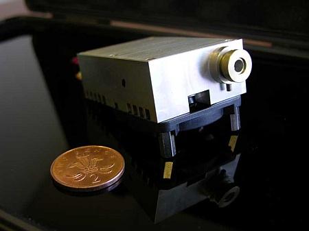 Laserbeamer naast two pence muntstuk