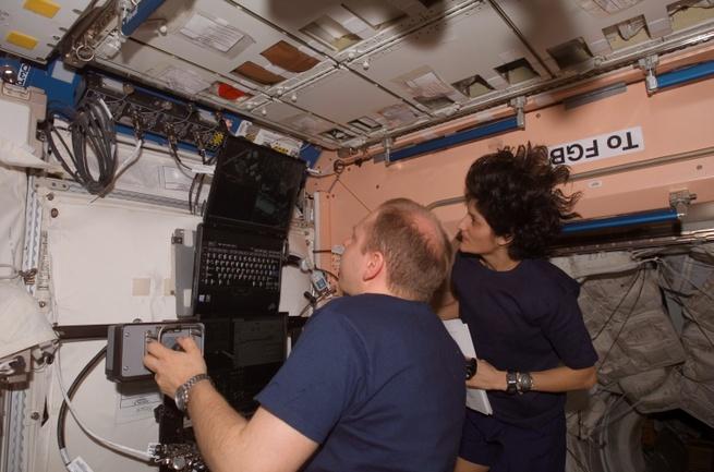 Astronauten gebruiken een laptop in het ISS