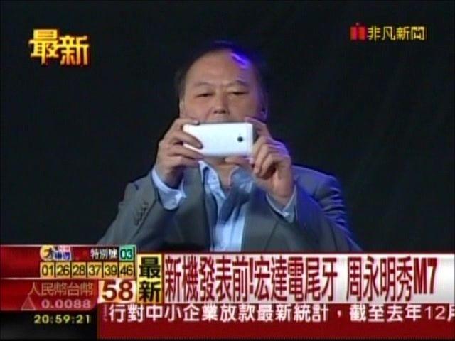 HTC-directeur Peter Chou neemt een foto met de M7