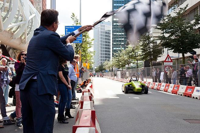 Minister Verhagen vlagt de studenten af, die zich in de waterstofauto niet hielden aan de geldende snelheidslimiet van 30km/u